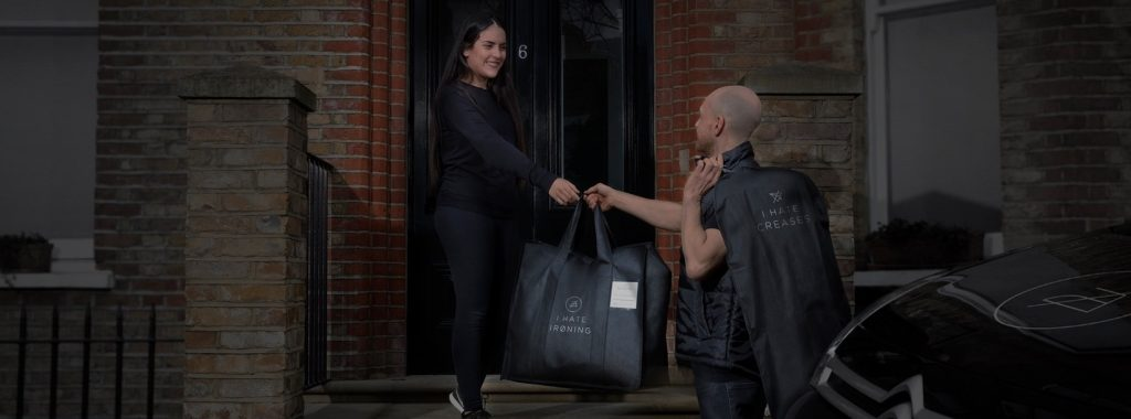 ihateironing driver delivers clean laundry in an ihateironing laundry bag to a happy customer